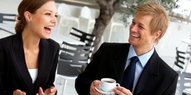 Two young business people enjoy coffee in an outdoor café.