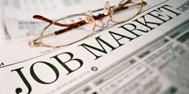 "Newspaper showing ""Job Market"", a pair of glasses rests on the newspaper."