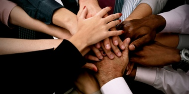 Hands in the center of a circle of diverse business people.